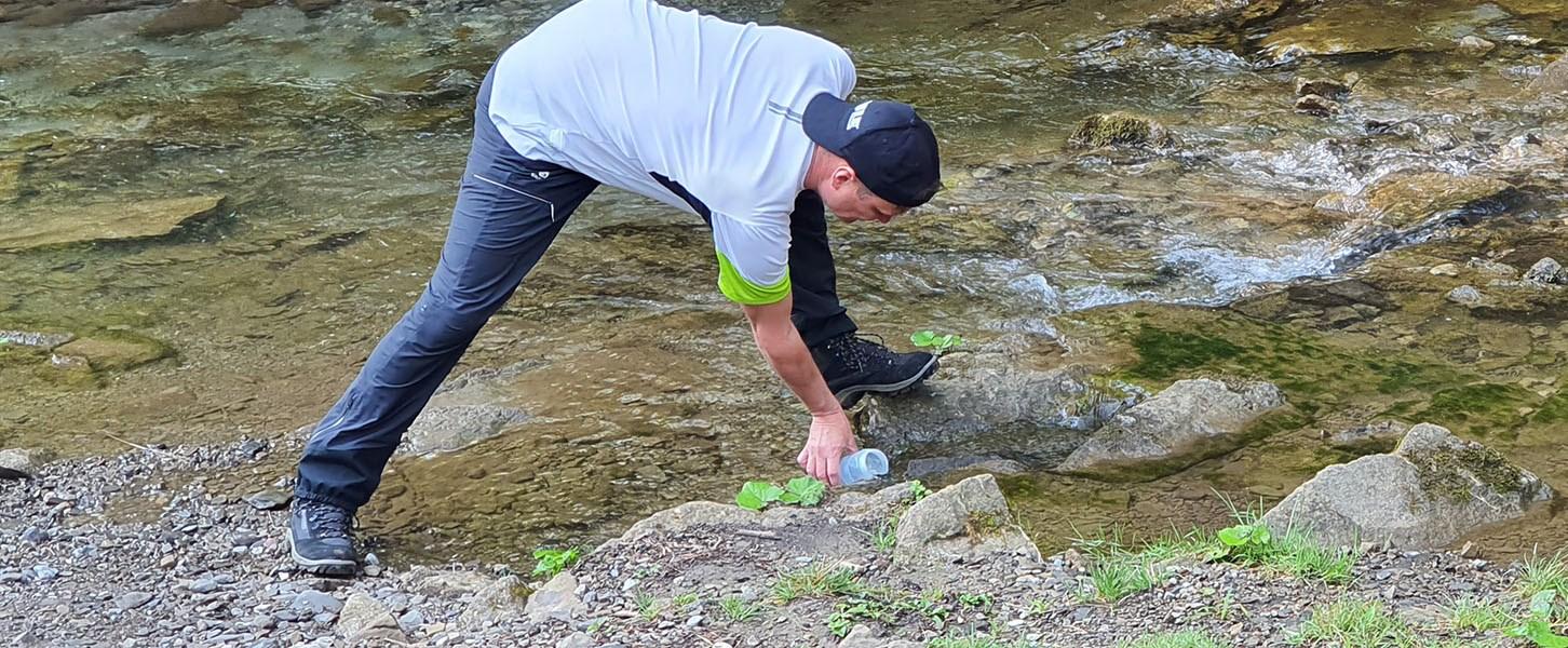 Muž nabírající vodu z řeky do filtrační lahve Quell NOMAD