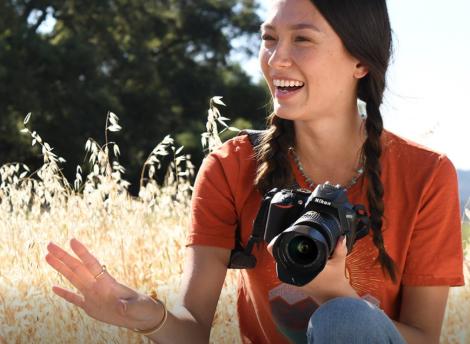 usmievajúca sa žena s digitálnym fotoaparátom Nikon D3500 Black v ruke