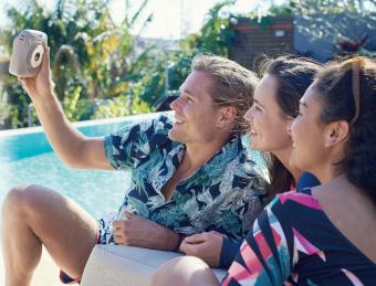 muž fotící selfie fotku u bazénu se dvěma ženami