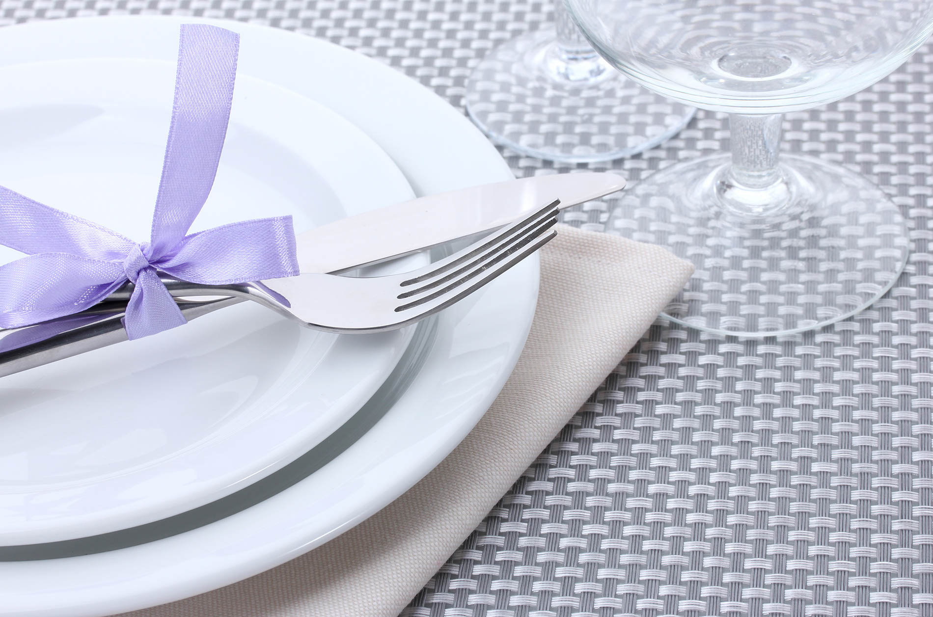 Nůž a vidlička Gourmet Excelent svázané mašlí a položené na prostřeném talíři