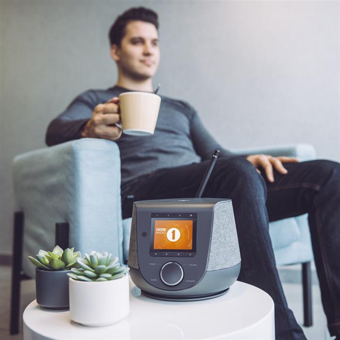 Digitální internetové radio na stolku a muž popíjející kávu