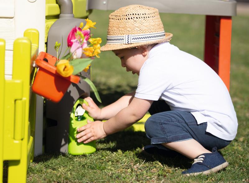 Chlapček napúšťajúci vodu do kanvičky z nádrže na dažďovú vodu