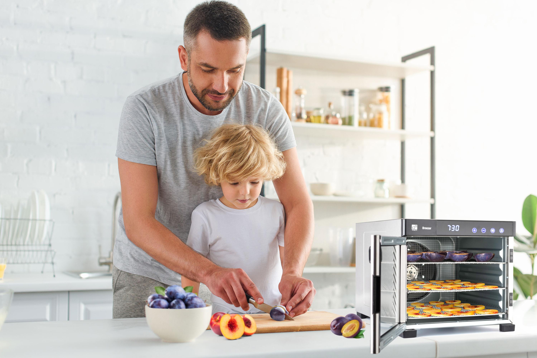 tatínek se synem připravující ovoce k sušení v sušičce G21 Breeze