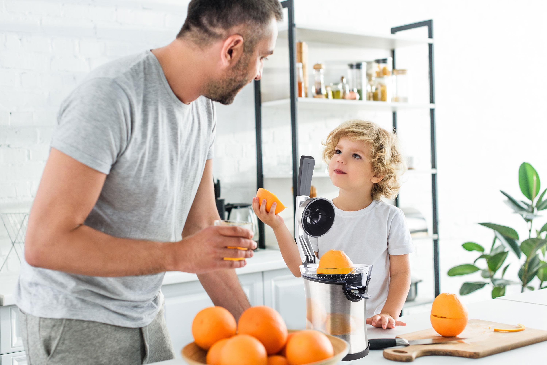 Táta s malým synem používající v kuchyni lis na citrusy G21 Active