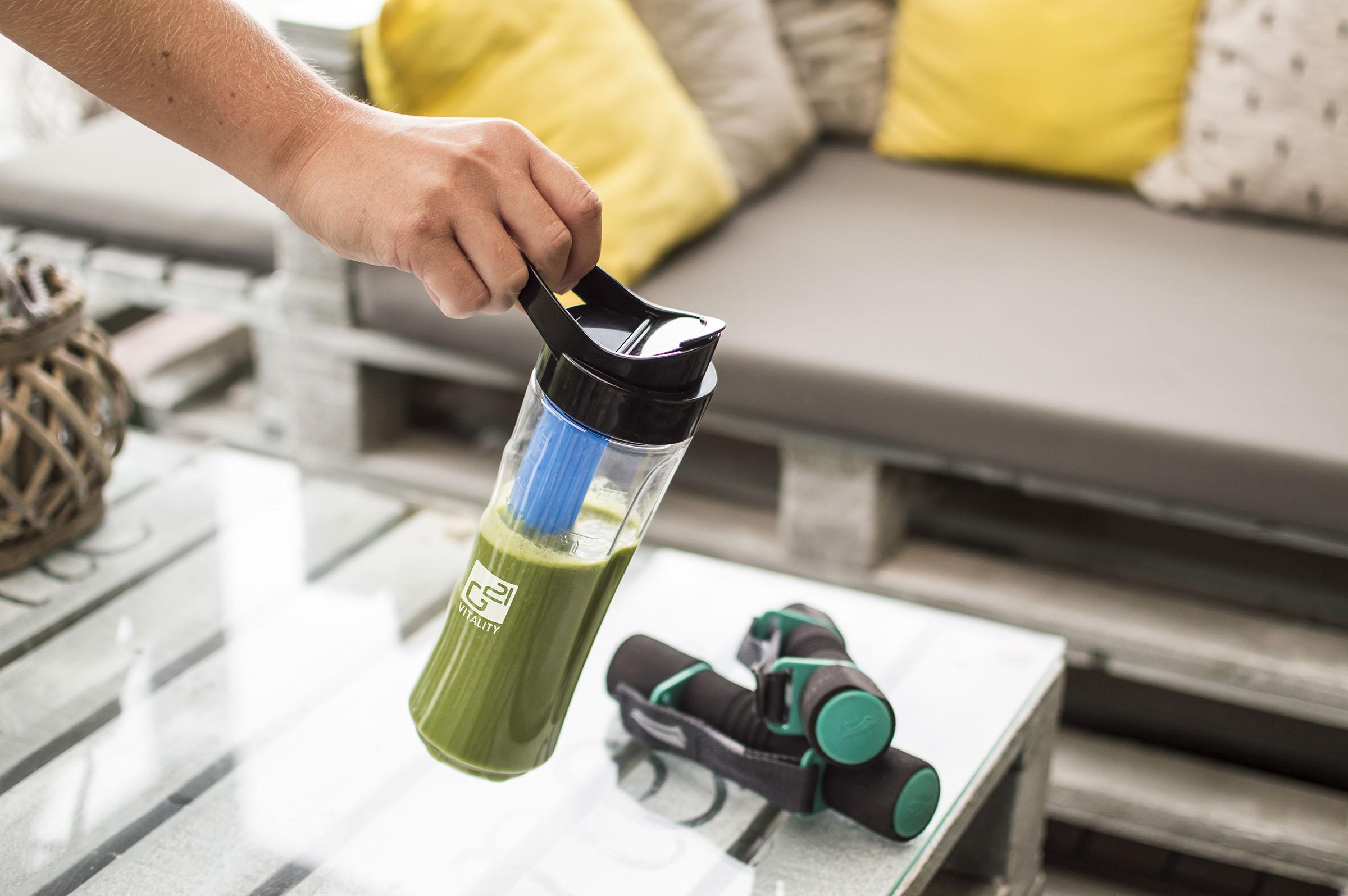 ruka držící smoothie maker nad stolem s odloženým vybavením na cvičení
