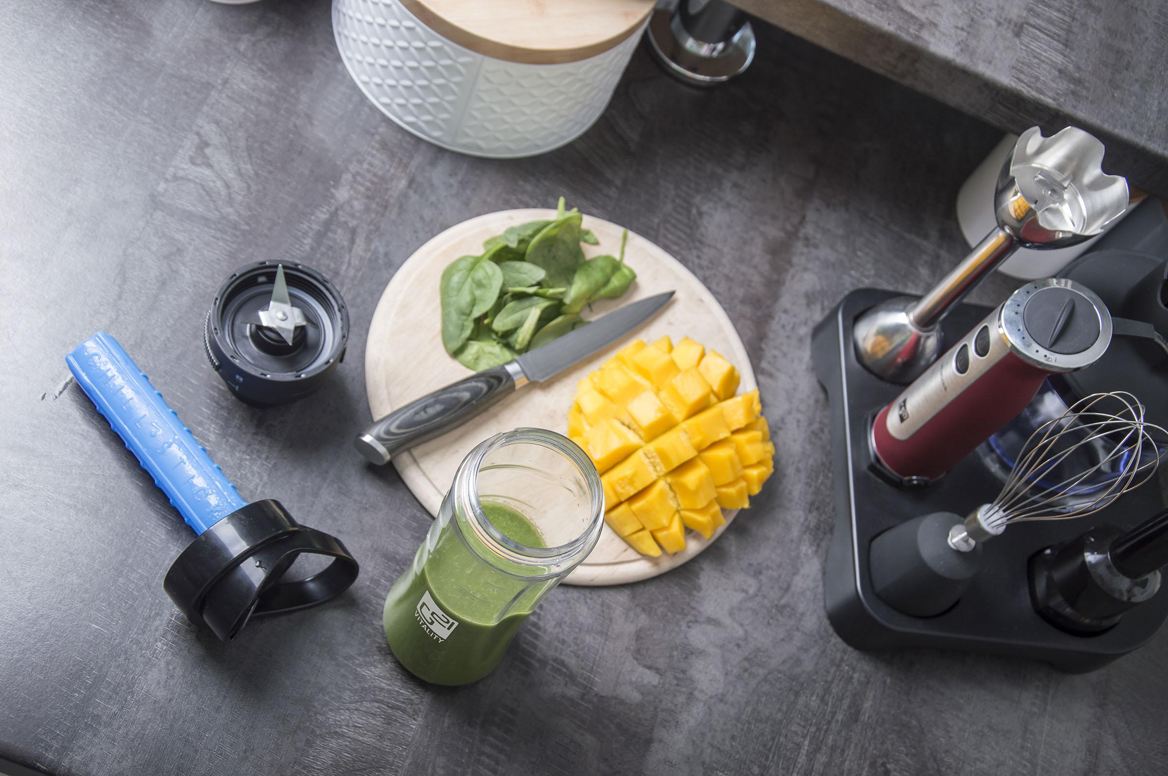 Smoothie maker na kuchyňské lince s namixovaným smoothie drinkem a připravenými surovinami