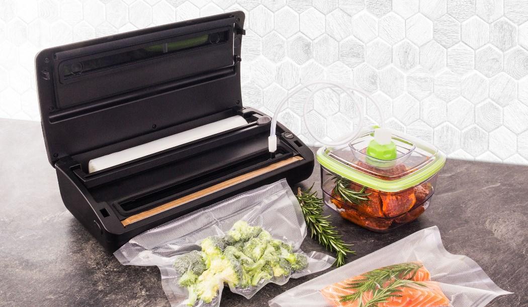 Vákuumozottzöldségfélék és lazac főzésre készen áll a Sous-vide G21 Akura tűzhely segítségével. Vákuum hegesztő G21 pácoló hús betöltött tartályba G21.