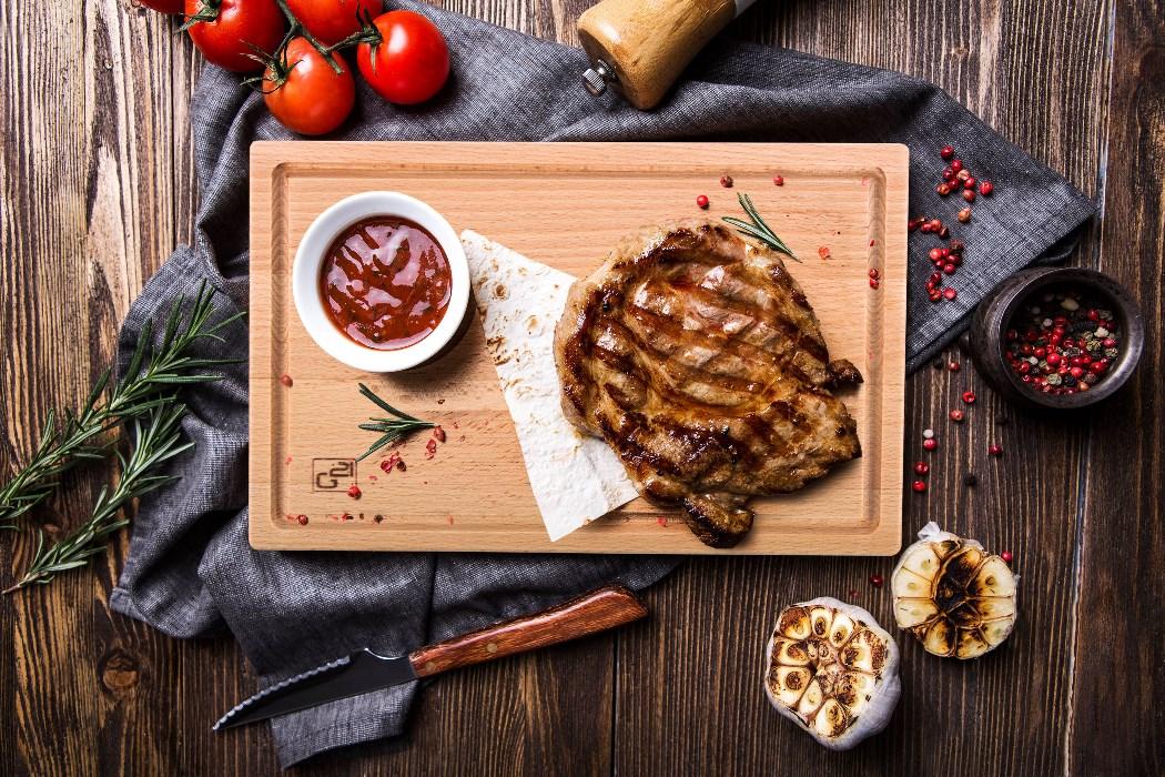 Grilovaný steak na servírovacím prkénku G21 s omáčkou v misce.