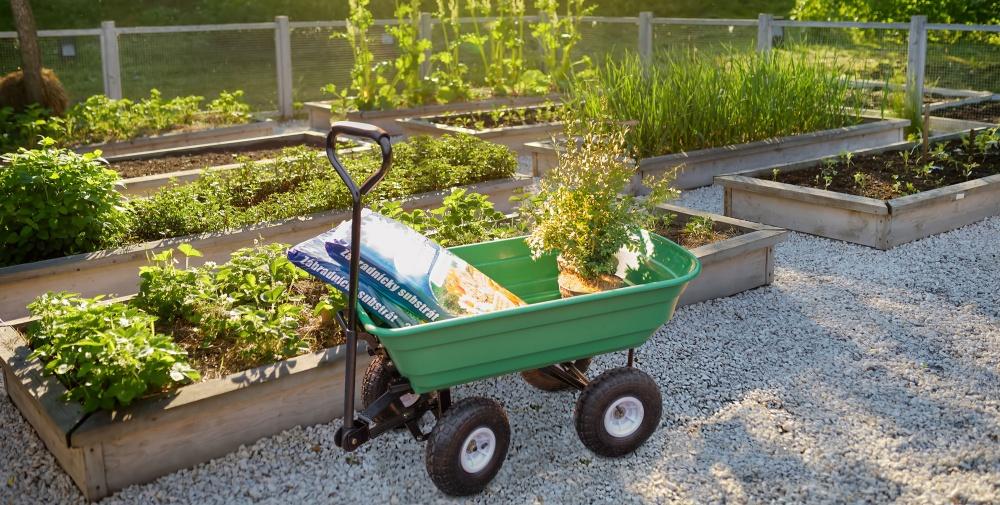 Zahradní vozík G21 mezi záhony s naloženou pytlovanou zeminou a květináči