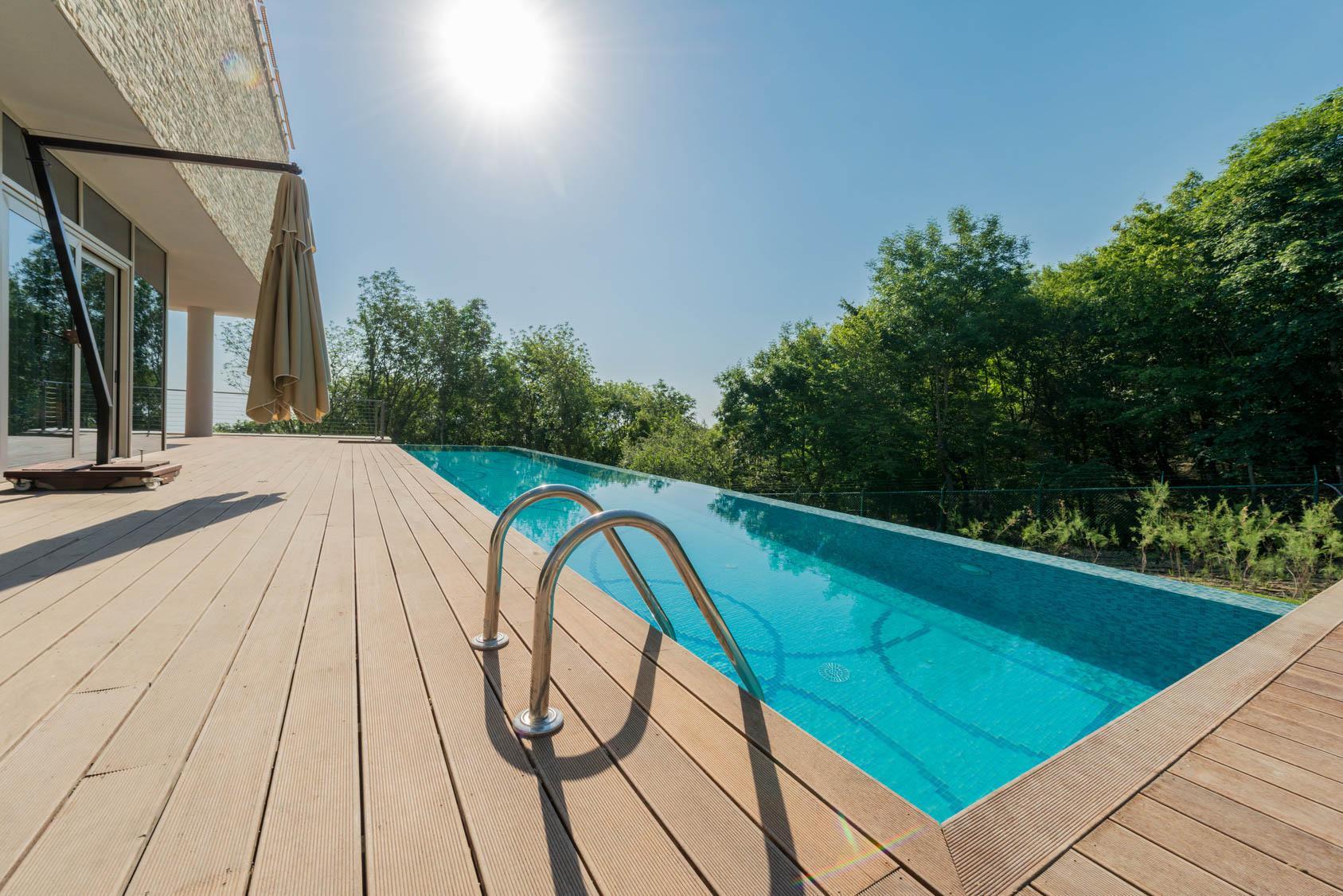 WPC terasový povrch okolo nekonečného bazénu pri dome