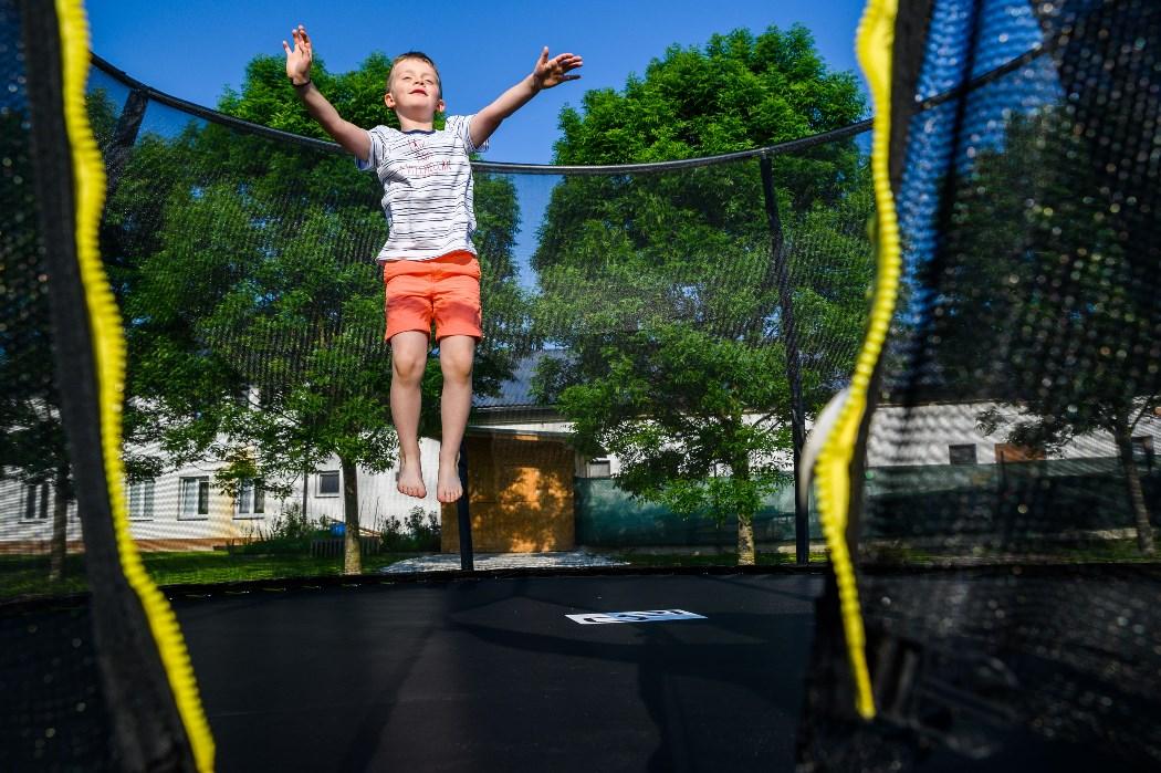 Ugráló kisfiú a G21 SpaceJump trambulinon védőhálóval.