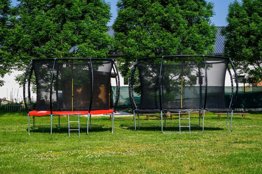 Trampolíny G21 SpaceJump s ochrannou sieťou na trávnatej ploche.