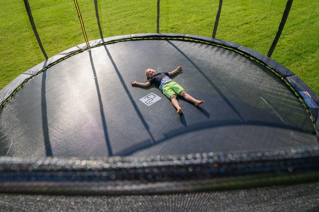 Chlapec vylézající zipovým otvorem z trampolíny G21 SpaceJump s ochrannou sítí.
